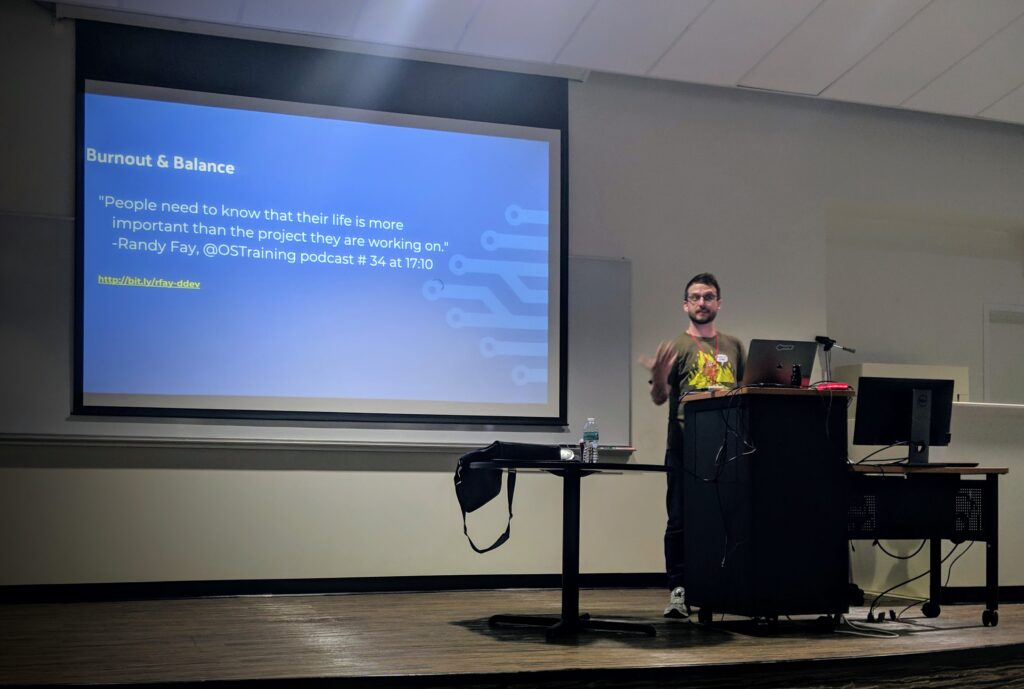 """Kevin presenting at Drupal Camp Florida. Slide is a quote from Randy Fay reading """"people need to know that their life is more important than the project they are working on"""""""