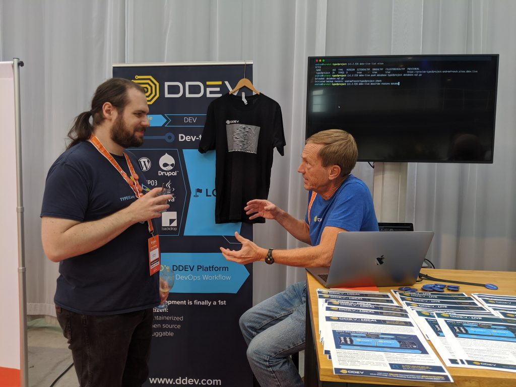 Randy Fay and @Codemonkey1988 talking and gesturing at the DDEV booth at TYPO3Con