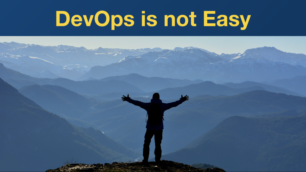 """Hiker overlooking an impressive mountain range with arms spread. Slide text reads """"DevOps is not Easy."""""""