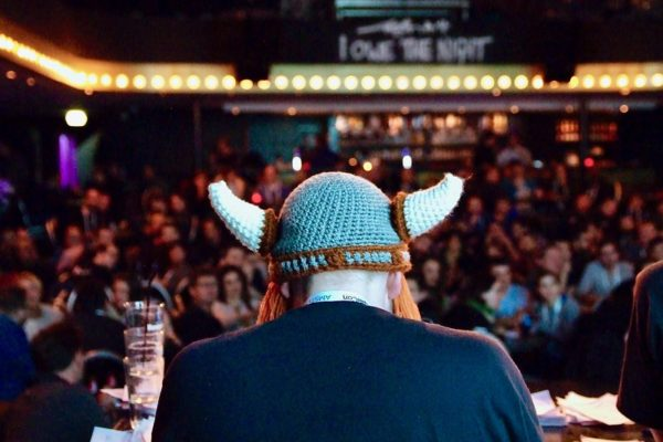 Hilmar looking out over the crowd as a juror on trivia night in a knit viking hat