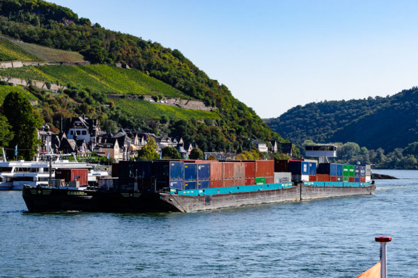 A two part barge with stacks of shipping containers on board travels down the Rhine in Germany